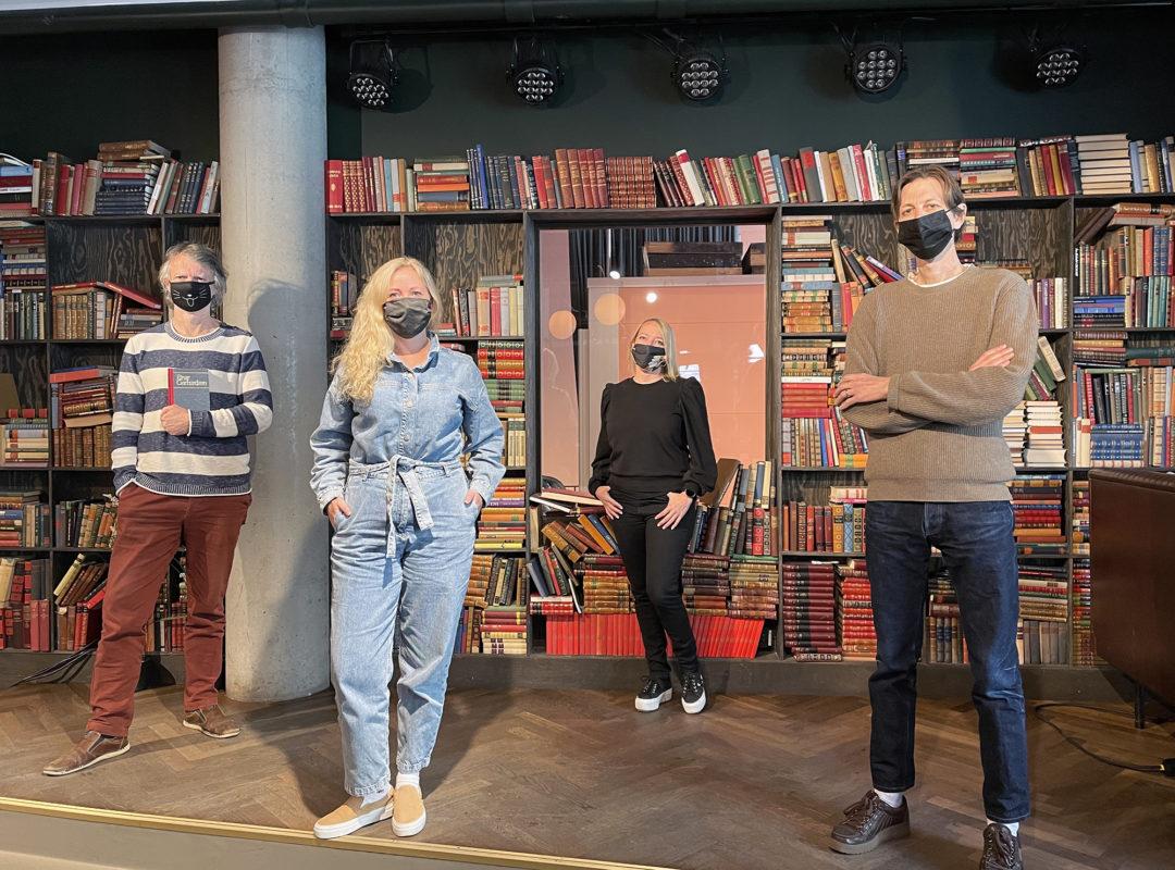 Erling, Aslaug, Maren og Knut står foran en bokhylle med en alvorlig mine. Alle har på seg munnind.