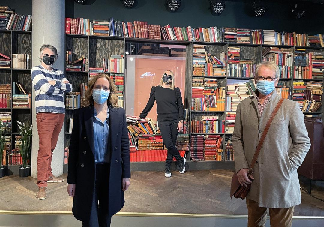 Erling, Hanna, Maren og Thomas står foran en stor bokhylle og ser mot kamera, alle har på munnbind.