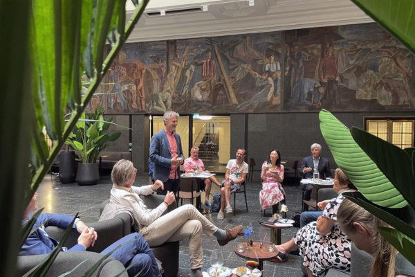 Flere mennesker samlet i et rom med freskomaleri på veggen og grønne planter i rommet. En mann (Erling Fossen) står og snakker og de andre sitter på stoler og i sofa og ser på mannen som snakker.