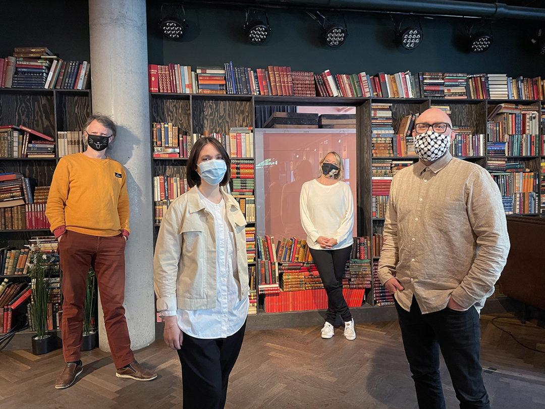 Erling Fossen, Hanna Maria Van Zijp, Maren Bjerkeng og Francis Brekke står foran en stor bokhylle og ser mot kamera. Alle har på seg munnbind.