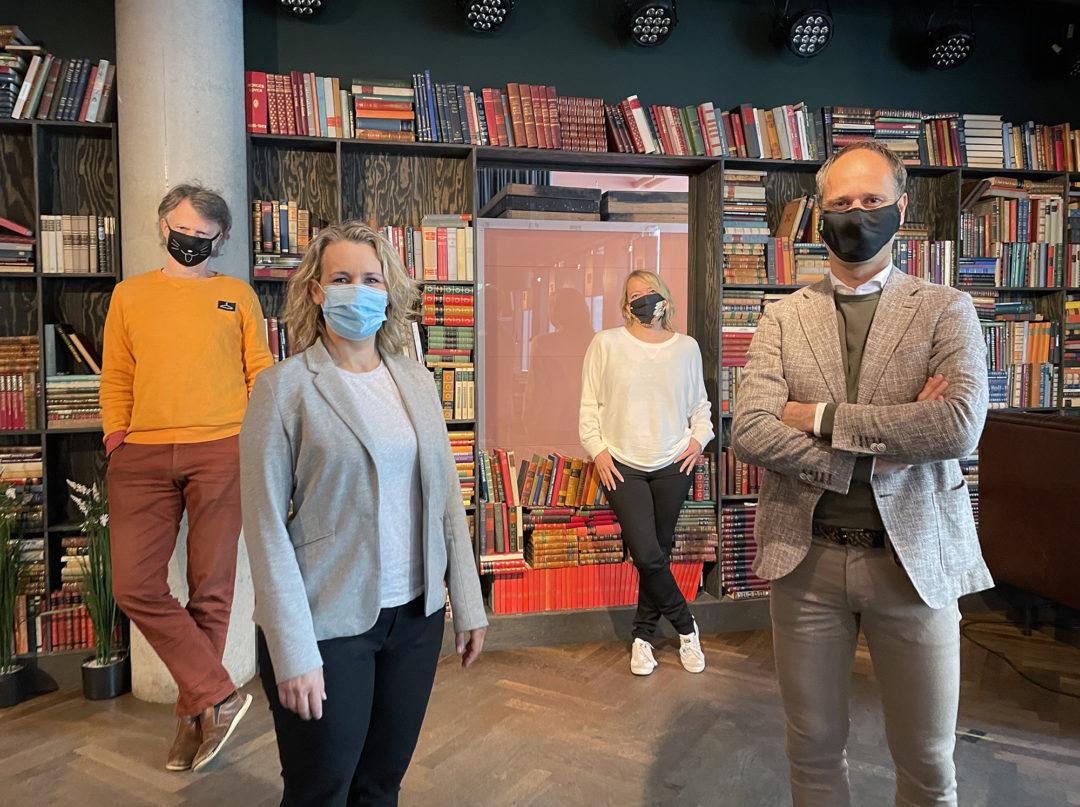 Erling Fossen, Eili Vigestad Berge, Maren Bjerkeng og Thomas Holth står foran en bokhylle fylt med bøker. Alle har på seg munnbind og ser mot kamera.