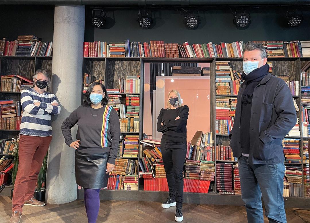 Erling Fossen, Nazneen Khan-Østrem, Maren Bjerkeng og Adnan Harambasic står foran en bokhylle fylt med bøker. Alle har på seg munnbind og ser mot kamera.