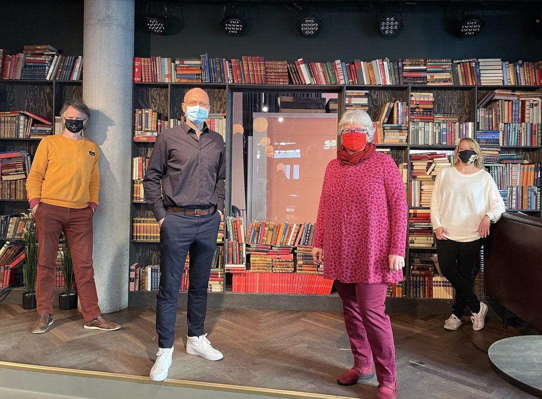 Erling Fossen, Jakob Krupka, Janne Wilberg og Maren Bjerkeng står foran en stor bokhylla og ser mot kamera. Alle har på seg munnbind.