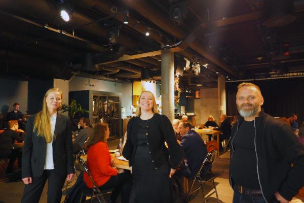 Emelie, Maren og Bjørnar står oppreist og smiler mot kamera. Bak dem sitter flere gruppe med mennesker og har workshop rundt flere bord.