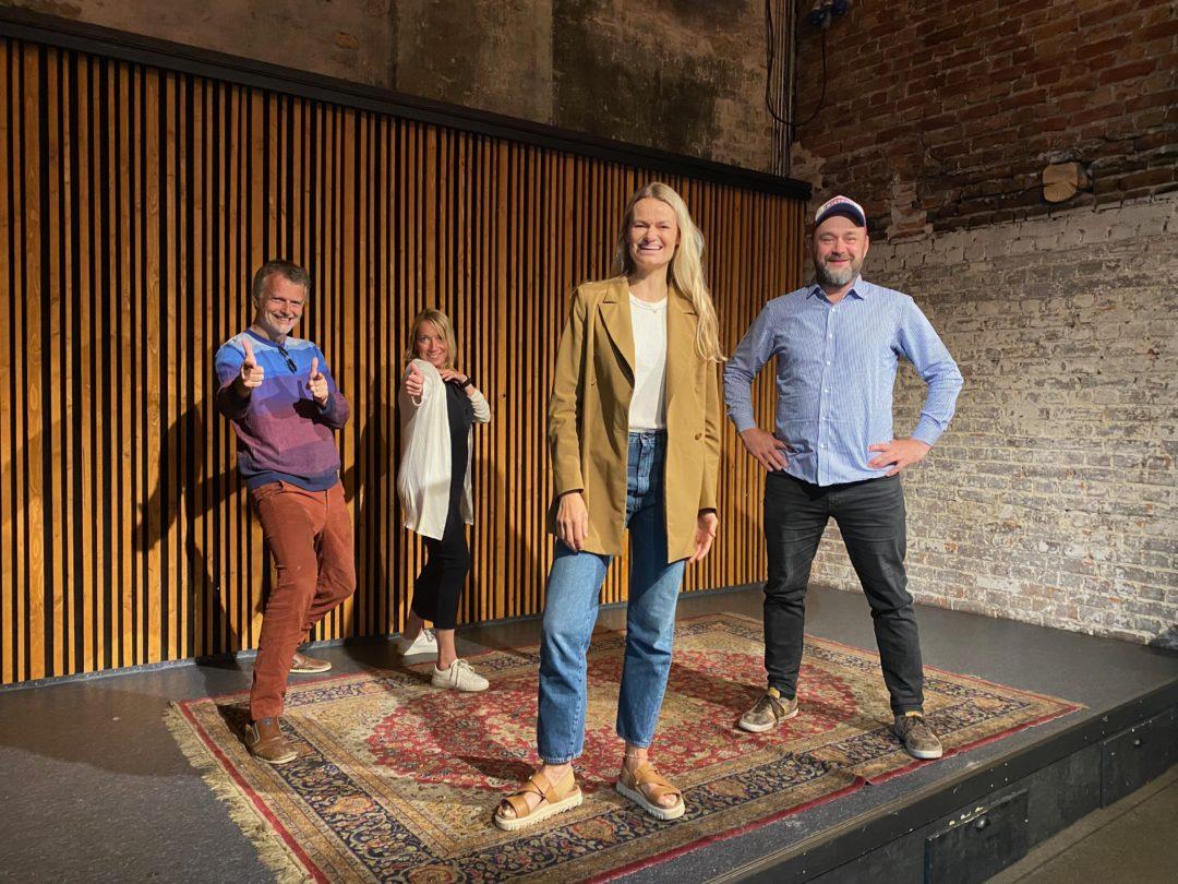 Erling Fossen, Maren Bjerkeng, Susanne Holzweiler og Runar Skjerven Eggesvik står på en liten scene og ser mot kamera. Erling og Maren tuller i bakgrunnen.