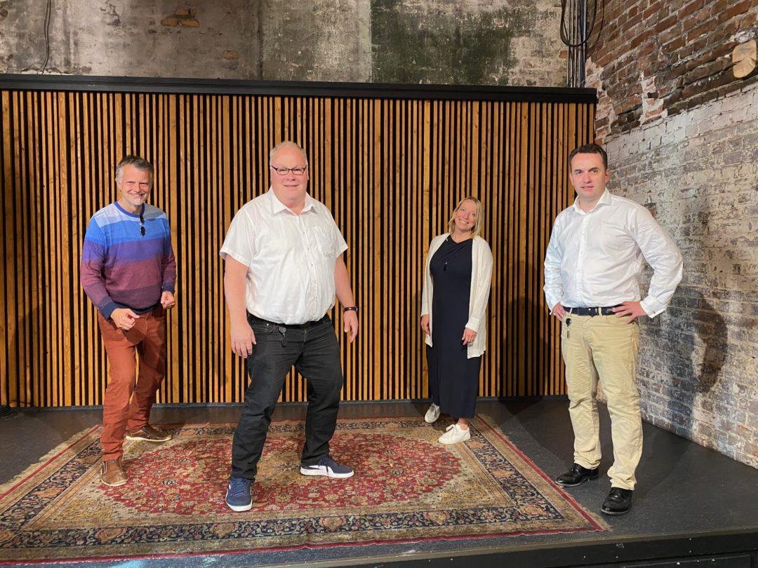 Erling Fossen, Bård Folke Fredriksen, Maren Bjerkeng og Stian Berger Røsland står på en liten scene og ser mot kamera. Erling og Maren tuller i bakgrunnen