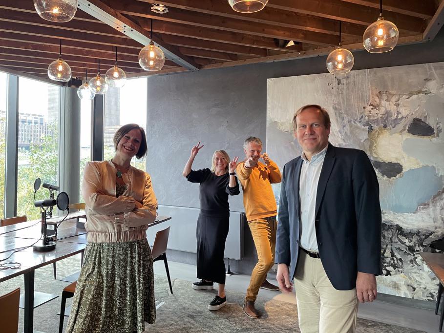 Hanna E. Marcussen og Jon Anders Henriksen står og smiler. Maren Bjerkeng og Erling Fossen lager ablegøyer i bakgrunnen