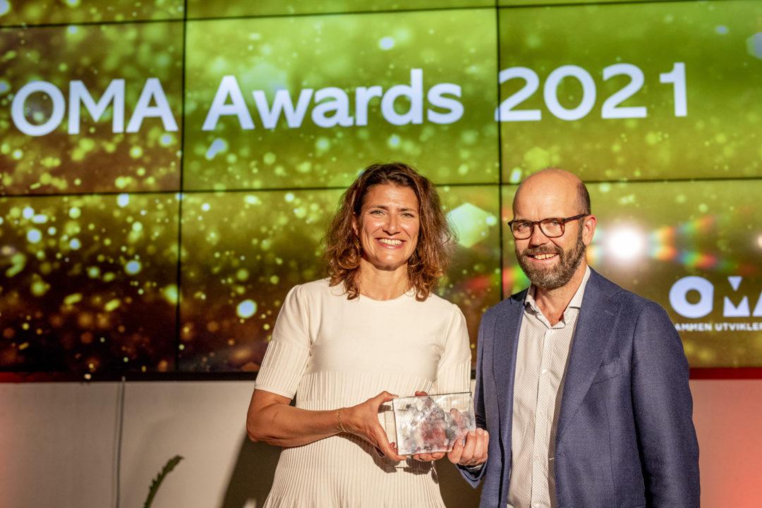 Sonja Horn, adm. dir. og Per Ola Ulseth, direktør prosjektutvikling i Entra står på en scene og smiler til kamera. Sonja holder prisen i hånda.