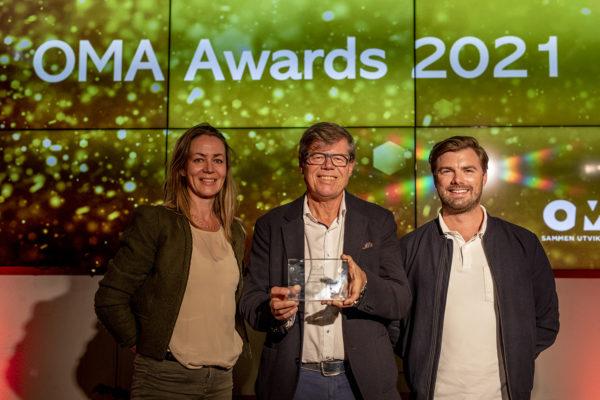 Tre personer (kvinne, mann og mann) står på en scene og smiler mot kamera. Mannen i midten holder en pris.